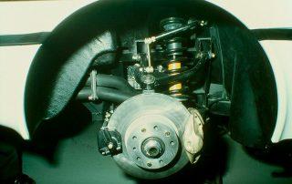 BMW M1 - Produktion, Doppelquerlenker - Hinterachsaufhängung rechts, mit Drehstab, Stoßdämpfer und Feder, Bremsscheibe mit Festsattel für Feststellbremse und Festsattel für Fußbremse, Vorbeiführung des Abgaszwischenrohres zum Schalldämpfer